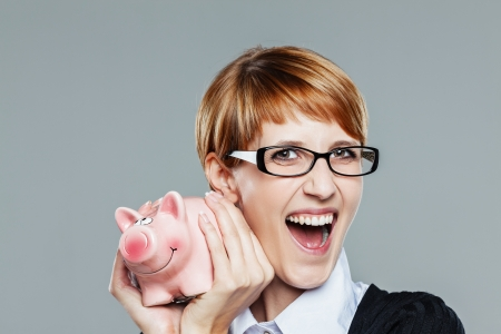 Business woman holding a little piggy bank and smiling isolated on grey
