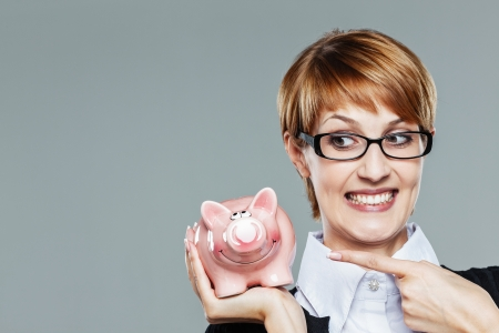 Business woman with glasses smiling and pointing finger to her piggy bank isolated on grey photo