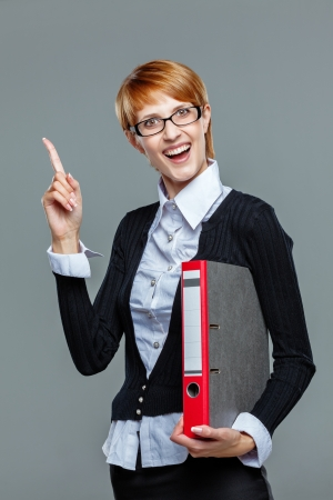 Young female office worker gesturing an idea with her finger and holding a folder with the other hand isolated on white