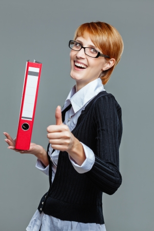Smart business woman holding a folder and showing thumb up isolated on grey photo