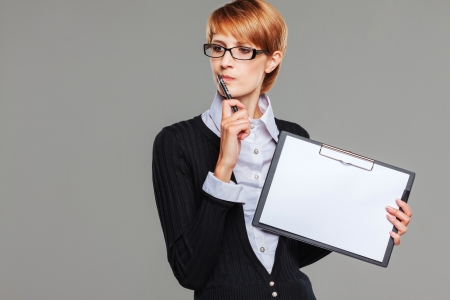 Attractive business woman holding a clipboard and thinking isolated on grey Stock Photo