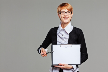 Attractive female office worker presenting a clipboard and pointing with a pen isolated on grey photo