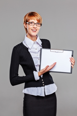 Smart business woman pointing at her clipboard and smiling isolated on grey photo