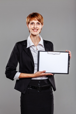 Smart business woman holding a clipboard isolated on grey Stock Photo