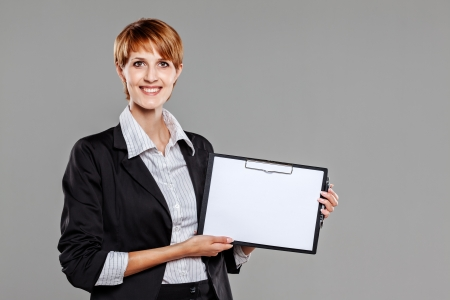 Young female employee holding a clipboard isolated on grey