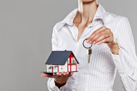 Young business woman presenting a model house and keys isolated on grey Stock Photo