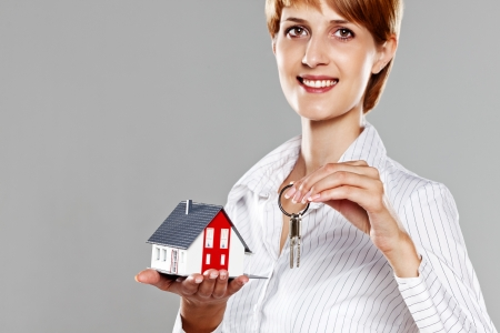 Friendly Real Estate Agent presenting a model house and keys isolated on grey