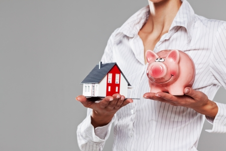 Female hands presenting a piggy bank and a model house isolated on grey photo