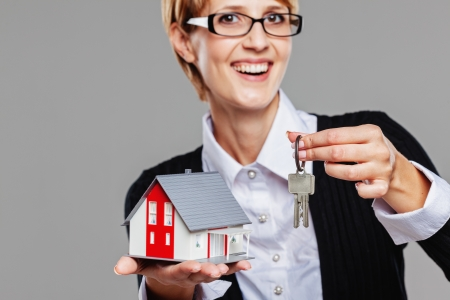 Attractive female real estate agent presenting a detached house model and keys isolated on grey Stock Photo