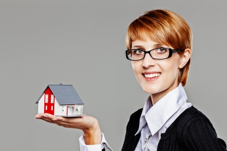 Attractive female real estate agent presenting a detached house model and smiling friendly to the camera isolated on grey