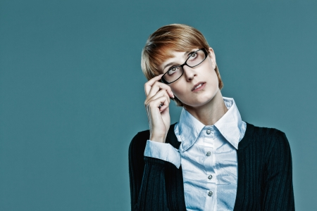 Business woman holding her glasses and looking up  Stock Photo