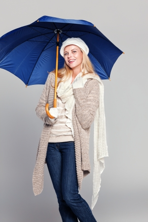 Beautiful woman in fall fashion holding an umbrella isolated on grey photo