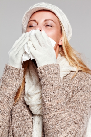 Woman holding a handkerchief and sneezing isolated on grey photo