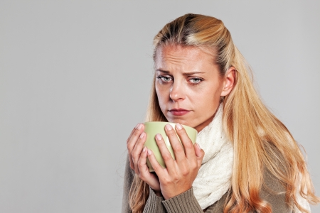 Ill woman holding a cup of tea isolated on grey Stock Photo