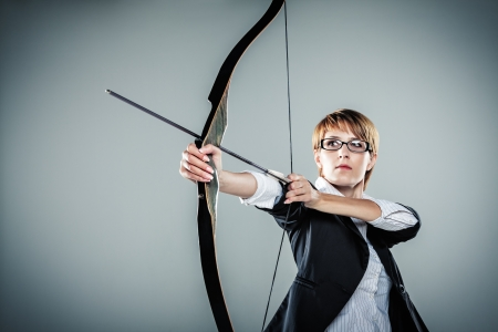 business woman standing: Business woman aiming with bow and arrow grey background