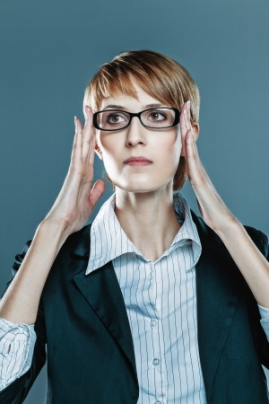 blinkers: Business woman focusing herself with hands on her spectacles blue background