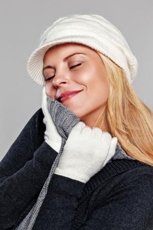 Woman enjoying her warm turtleneck sweater isolated on grey