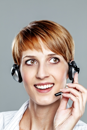 Business woman with headset isolated on grey photo