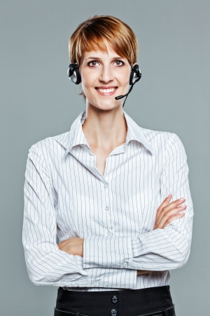Business woman with arms crossed and headset isolated on grey  Stock Photo
