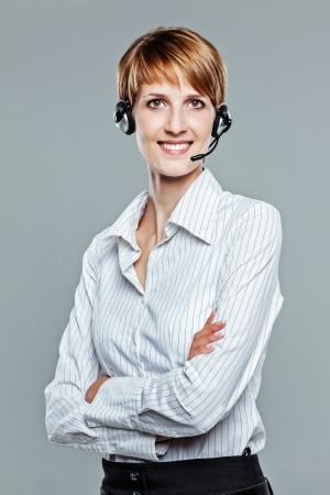 Business woman with arms crossed and headset on smiling to the camera isolated on grey photo