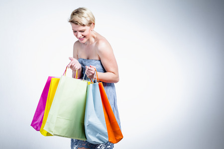 Blonde woman looking to her shopping bags