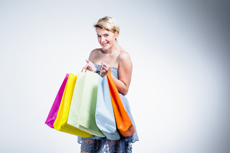 Blonde woman smiling and holding paper bags