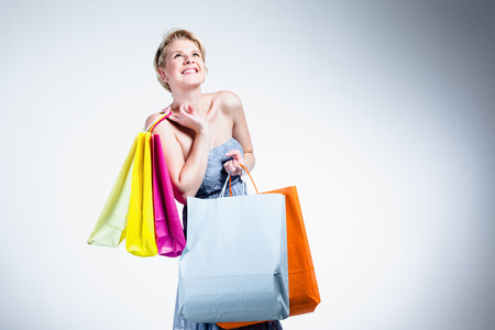 Woman looking up smiling and holding shopping bags photo