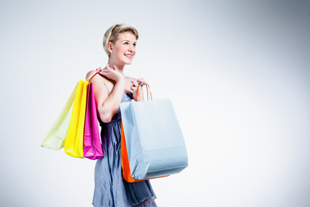 Blonde woman smiling and holding shopping bags  Stock Photo