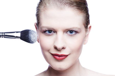 Close up of young woman with make up brush isolated on white Stock Photo