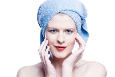 Young beauty with blue towel around her head isolated on white photo