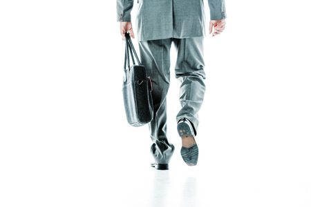 jetsetter: Backview of legs and hands of a businessman carrying a bag isolated on white