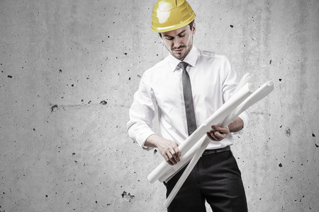Architect sorting plans in front of a concrete wall Stock Photo