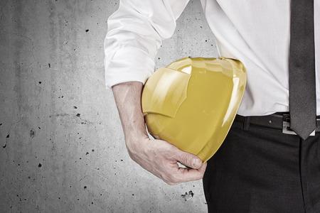 손 콘크리트 벽 앞에 노란색 하드 모자를 들고