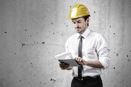 Architect working with a touch pad and holding a plan Stock Photo