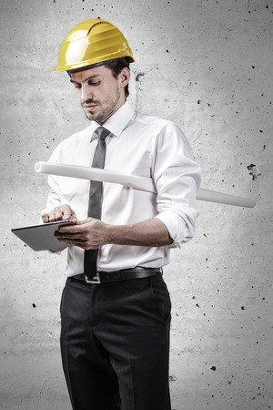 Architect holding a plan and working on a touchpad in front of a concrete wall