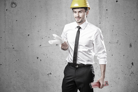 Engineer with plans and spirit level in front of a concrete wall photo