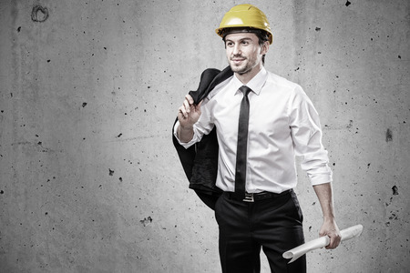 Architect with jacket over his shoulder and plan in hand photo