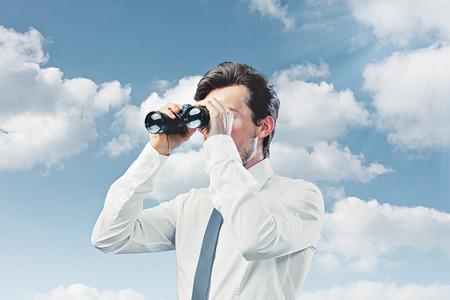 Businessman with binocular blue sky photo