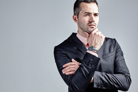 Fashionable businessman thinking with hand at chin isolated over grey