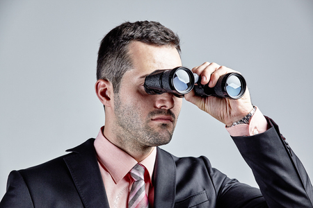 observing: Businessman observing with binoculars isolated over grey
