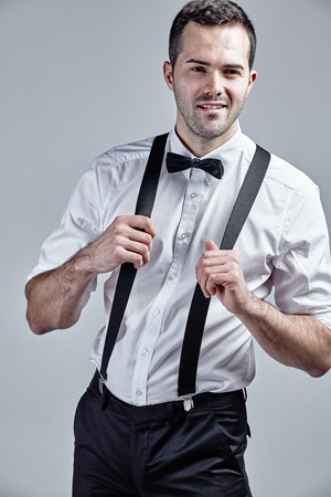 white beard: Fashionable man with suspenders and bow tie isolated over grey