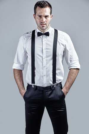 role models: Portrait of handsome man with bow tie and suspenders isolated over grey Stock Photo