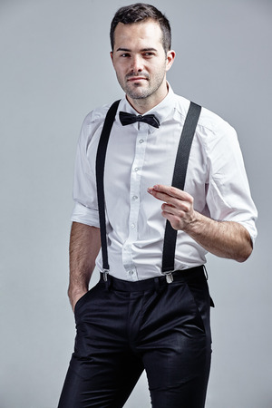 flicking: Fashionable man with bow tie and suspenders flicking fingers isolated over grey