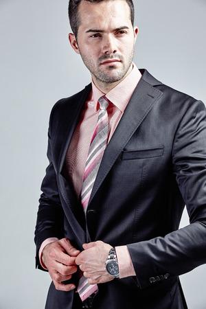 vistiendose: joven y exitoso hombre de negocios que consigue vestido aislado sobre gris Foto de archivo