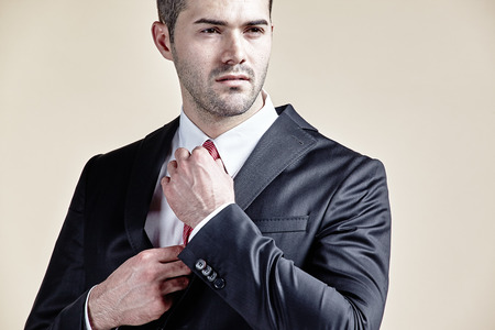only adult: Confident businessman preparing his tie isolated
