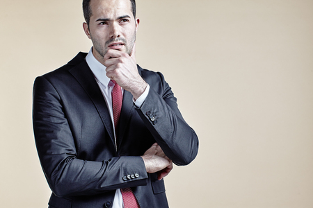 chin: Businessman with hand at chin isolated Stock Photo