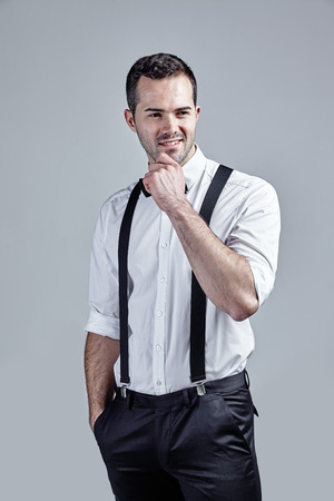 Young man in white shirt wearing suspenders isolated over gray