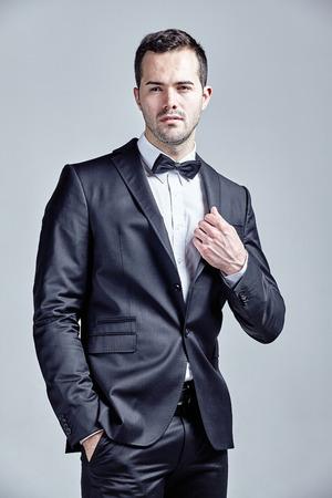 lazo negro: hombre joven que llevaba pajarita y traje negro aislado sobre gris Foto de archivo