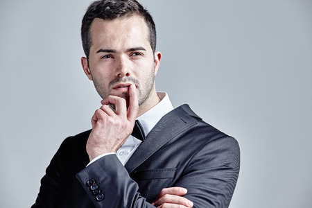 Thoughtful young man pointing finger over his lips isolated over grey Stock Photo