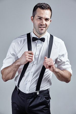 Young man with suspenders wearing white shirt and smiling isolated over grey